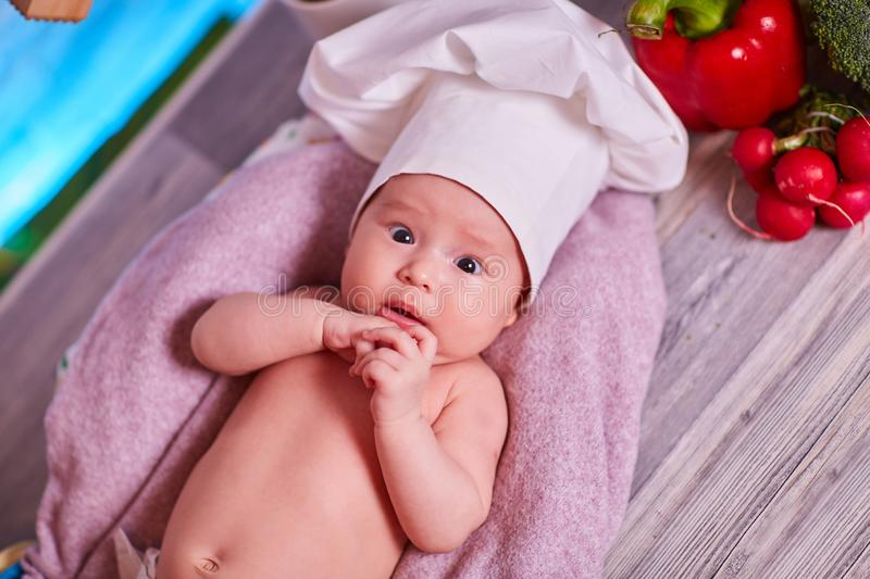 Child, baby girl lies on the kitchen table in a chef`s cap - next to him are vegetables, bell pepper, radish, broccoli, proper royalty free stock photography