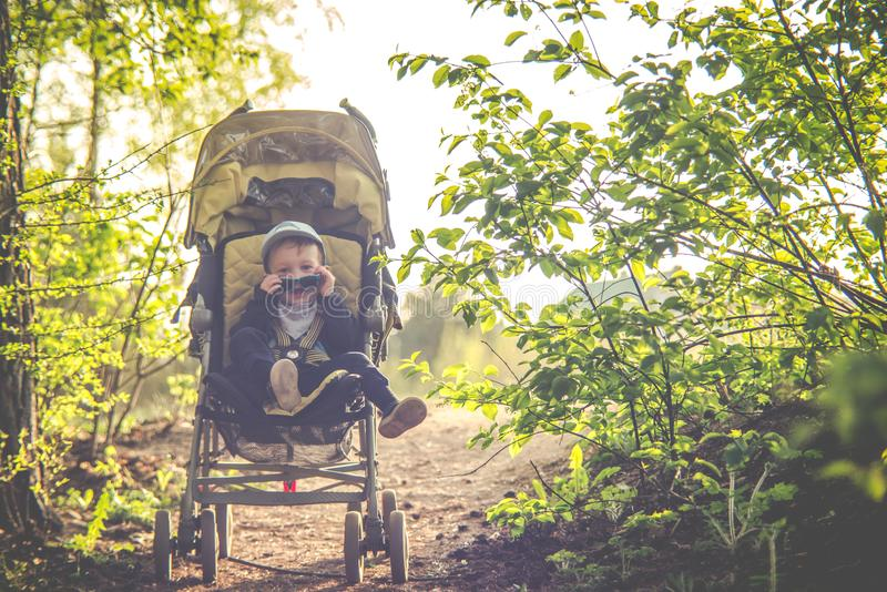Child in baby stroller outdoors spring stock photography