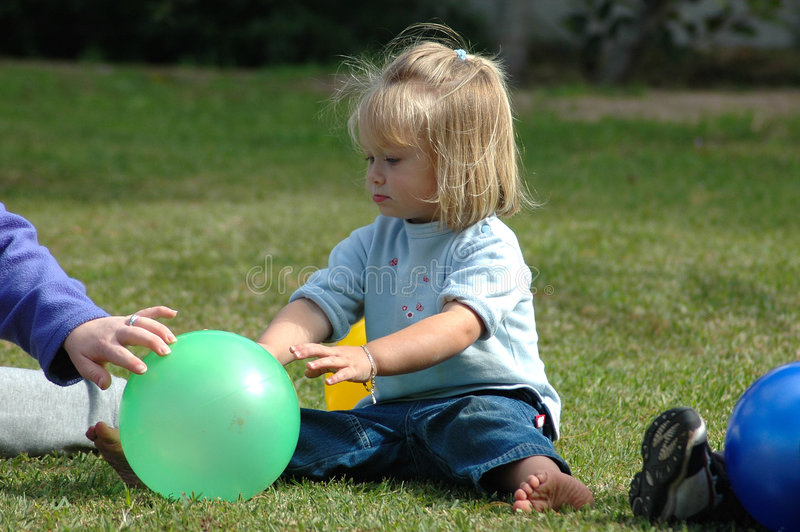 Child with ball. An active blond little caucasian white girl toddler enjoying herself by playing with a green ball sitting on the lawn in the backyard at stock photo