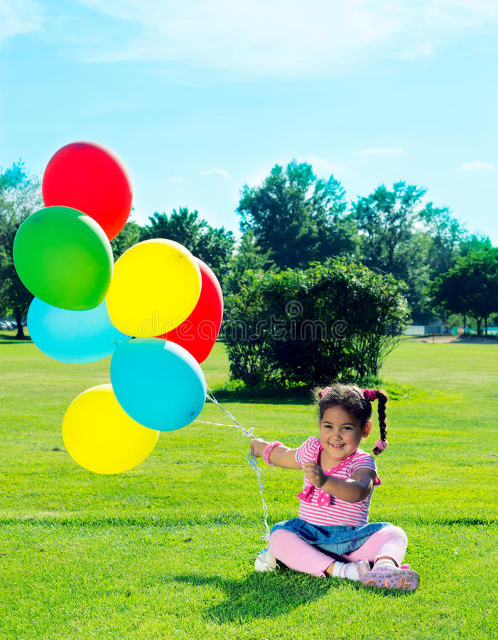 Child with balloons on the field stock image