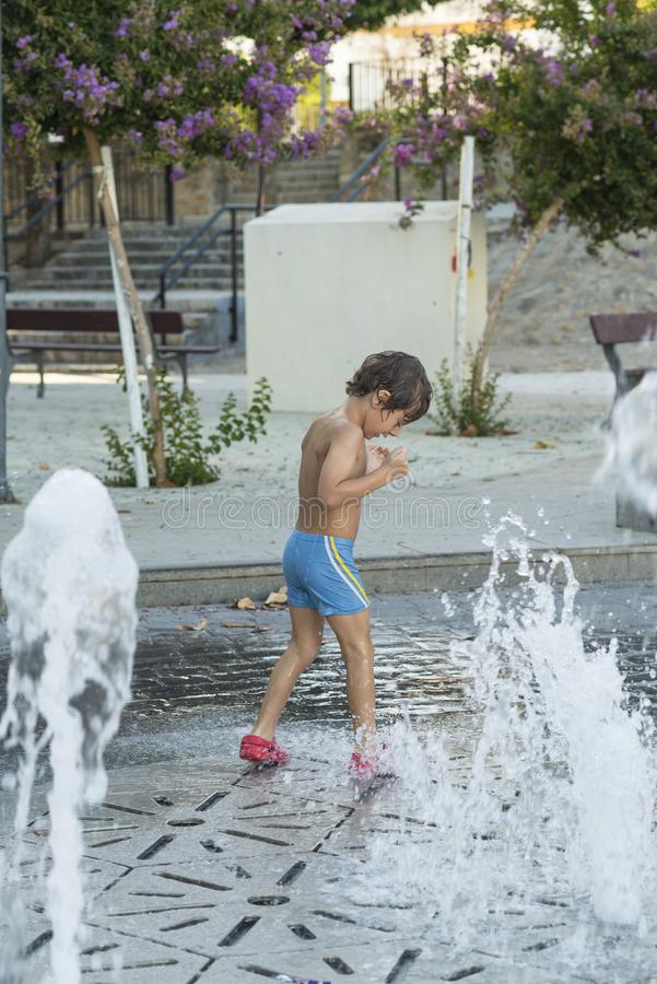 Child playing with water jets from a fountain. Child in bath clothes playing with water jets from a fountain located in the street. Childhood and summer concepts royalty free stock image