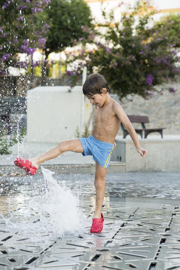Child playing with water jets from a fountain. Child in bath clothes playing with water jets from a fountain located in the street. Childhood and summer concepts stock photography