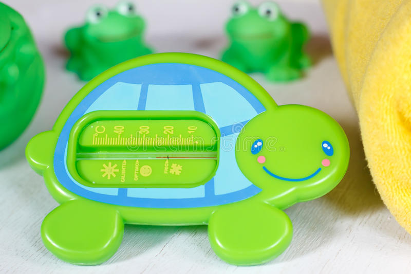 Child bath thermometer and bath toys stock photos