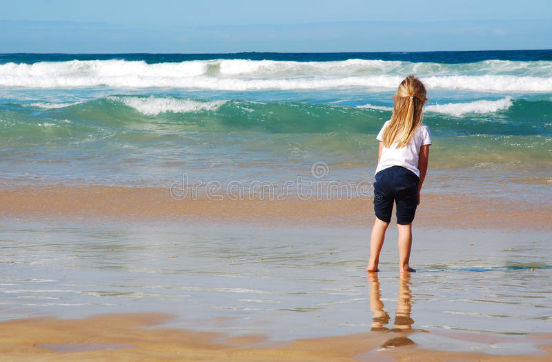Child on beach. Back view of a little Caucasian girl standing bare feet in the water watching the ocean stock image