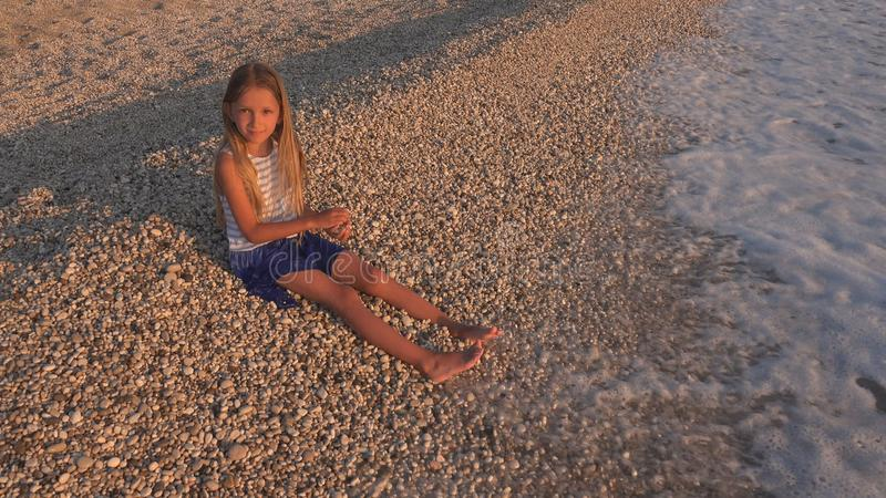 Child on Beach, Kid Playing at Sunset, Girl Throwing Pebbles in Sea Water royalty free stock photos