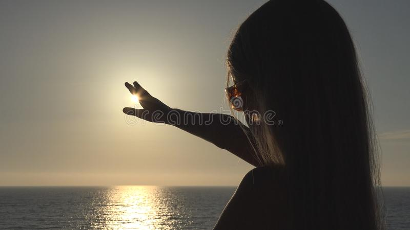 Child on Beach, Kid Silhouette Playing in Sunset, Girl Hand in Sun Rays, Beam royalty free stock photography
