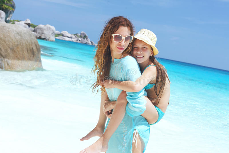 Child on a beach. Mother with her 8 years old daughter resting on a tropical beach during summer vacations stock photos
