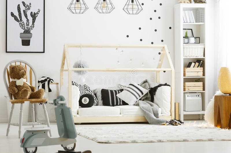 Child bedroom with wood bed. Rocking scooter, lamps and chair stock photography
