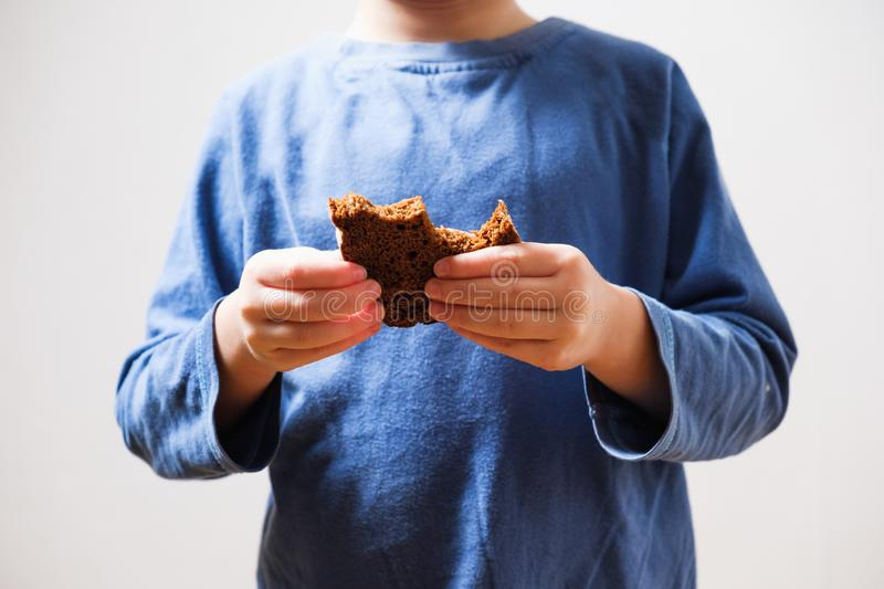 Child beggar eating cheap bread. Poor children and people donations Volunteers Concept. Child beggar eating cheap dirty bread. Poor children and people stock image