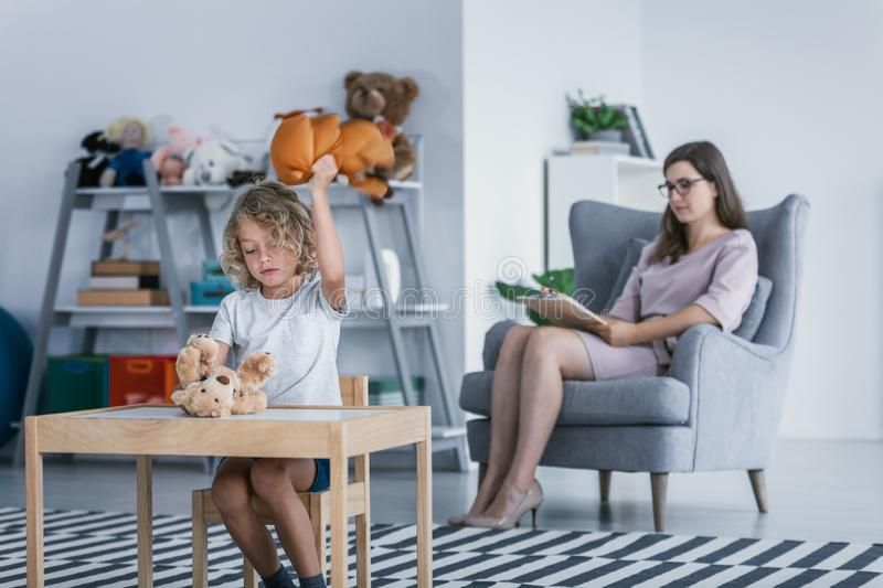 A child with behavioral problems hitting a teddy bear during a therapeutic meeting with a therapist in a. A child with behavioral problems sitting by a table and royalty free stock photo