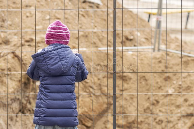 Child behind the fence. Small child behind a metal fence with his back to the camera stock photo