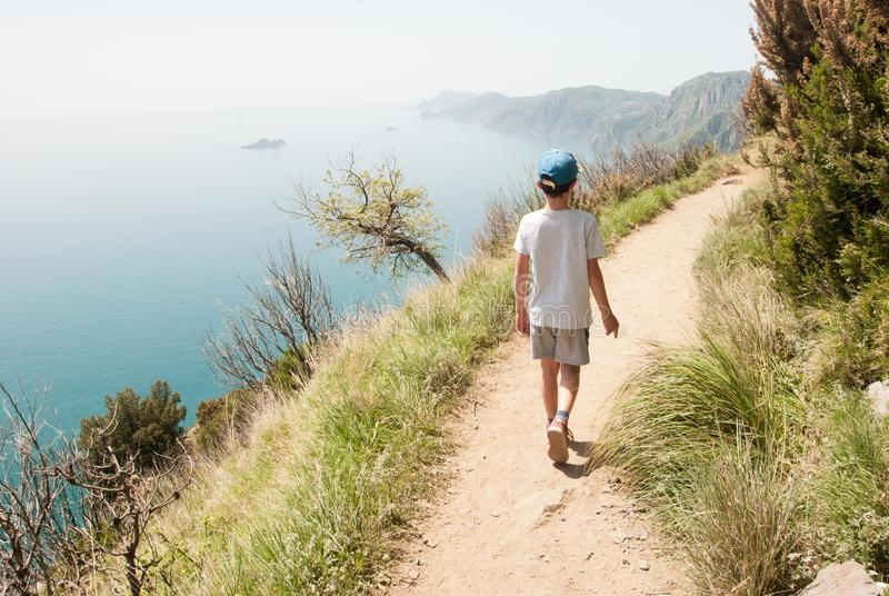 Child from behind walks on the path of the gods with panoramic sea views royalty free stock photography