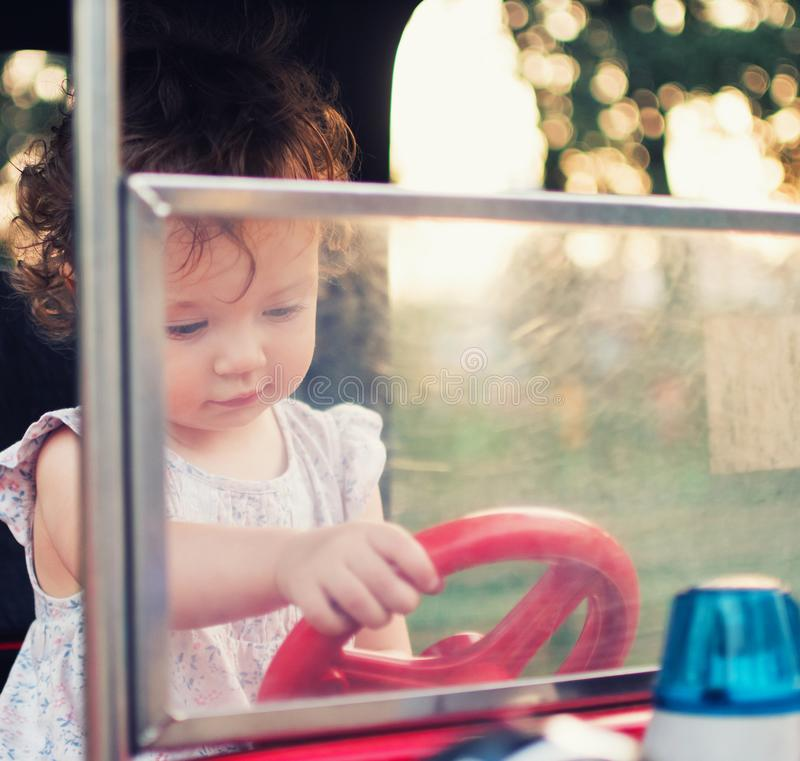 A child behind the wheel of a toy car. Toddler girl in the carousel amusement park stock photo