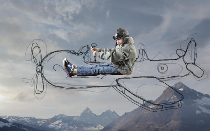Child being an aviator. Child pretending to drive a drawn plane and being an aviator stock photos