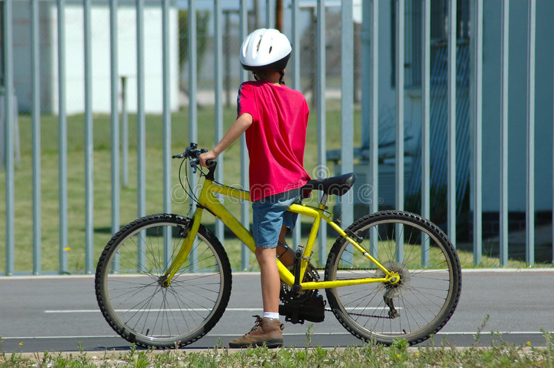 Child on bicycle. A boy child with colorful clothes and white helmet on a bicycle watching other kids in front of a school building