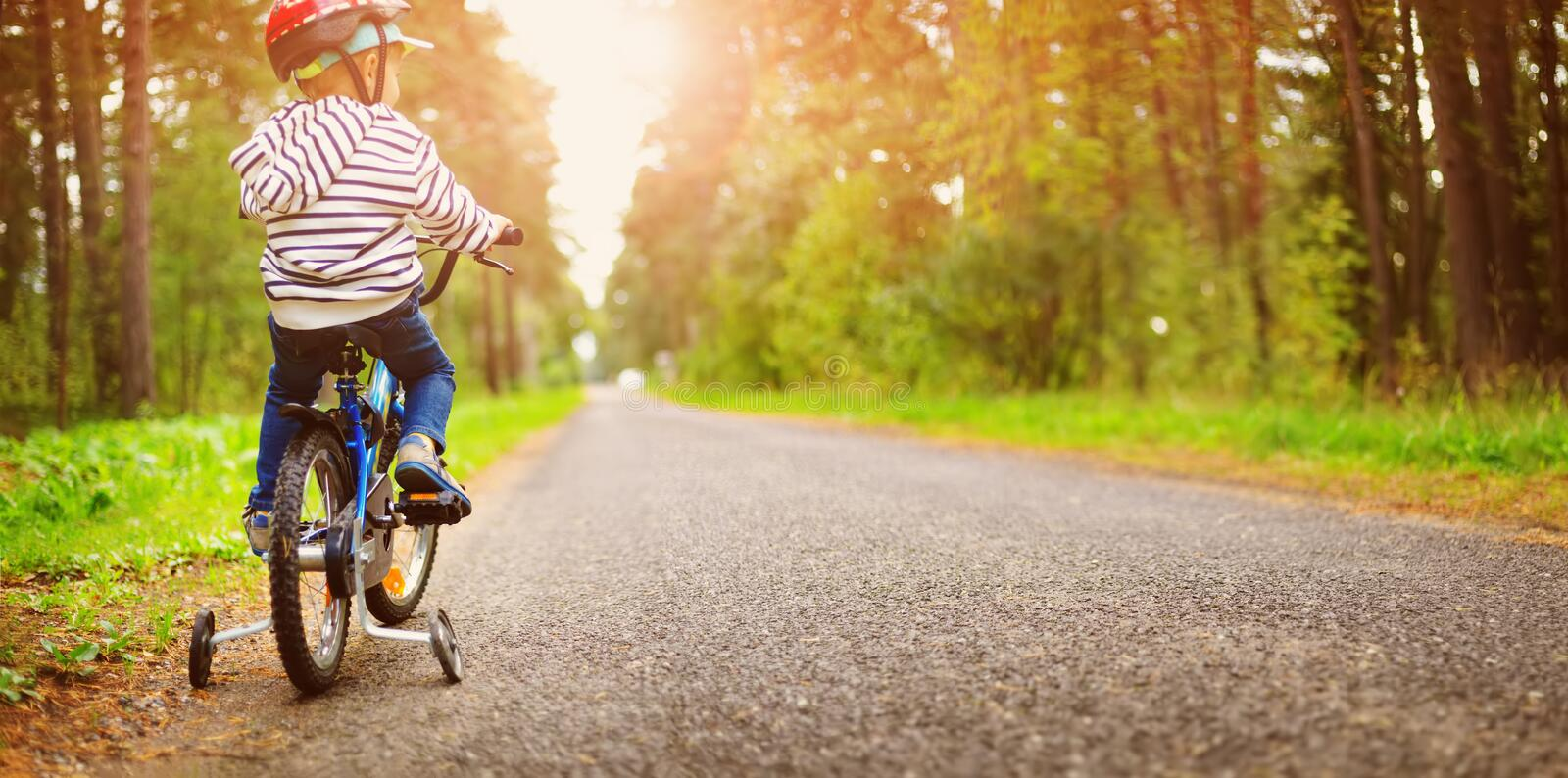 A child on a bicycle in helmet. On asphalt road stock photo