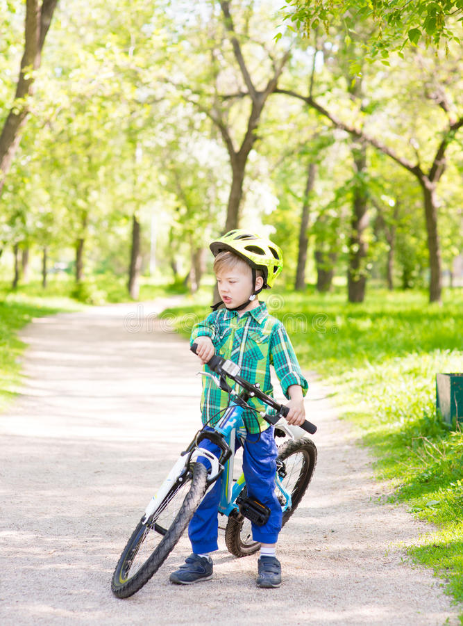 Child with a bicycle in a summer park royalty free stock photography