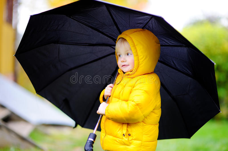 Child with big black umbrella in the rain. Little boy walking at rainy cloudy autumn weather. Child with big black umbrella in the rain. Fall outdoor activity royalty free stock photo