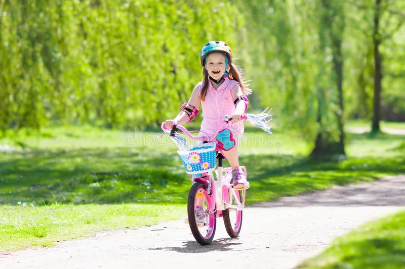 Child on bike. Kids ride bicycle. Girl cycling. Child riding a bike in summer park. Little girl learning to ride a bicycle without training wheels. Kindergarten stock image