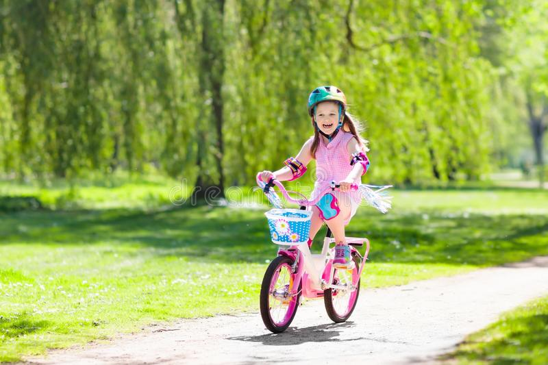 Child on bike. Kids ride bicycle. Girl cycling. Child riding a bike in summer park. Little girl learning to ride a bicycle without training wheels. Kindergarten royalty free stock photos