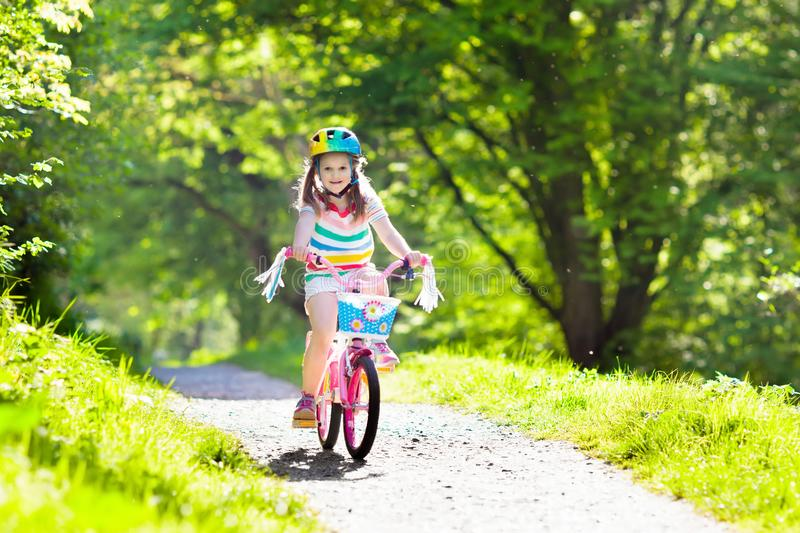 Child on bike. Kids ride bicycle. Girl cycling. Child riding a bike in summer park. Little girl learning to ride a bicycle without training wheels. Kindergarten stock images