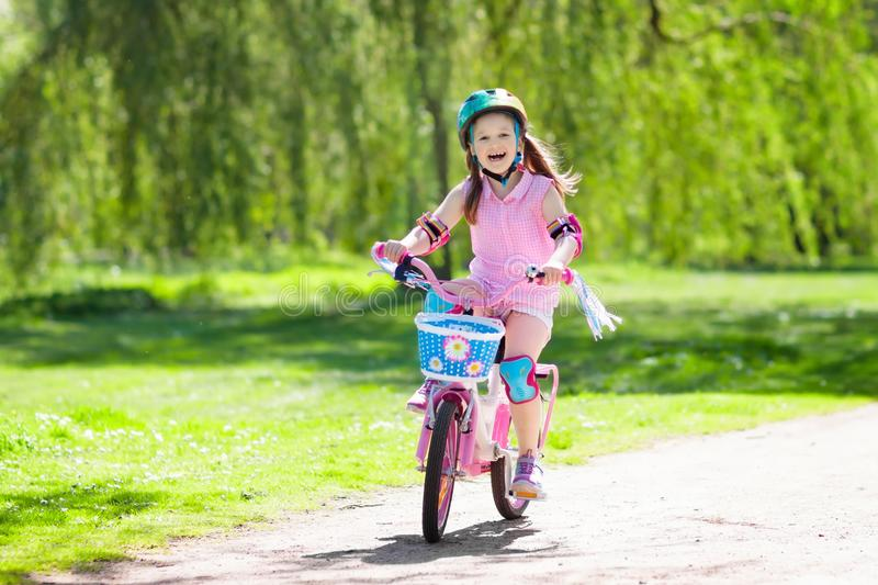 Child on bike. Kids ride bicycle. Girl cycling. stock photos