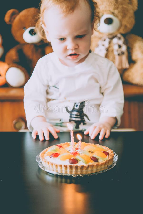 Child and birthday cake. With burning candles stock photography