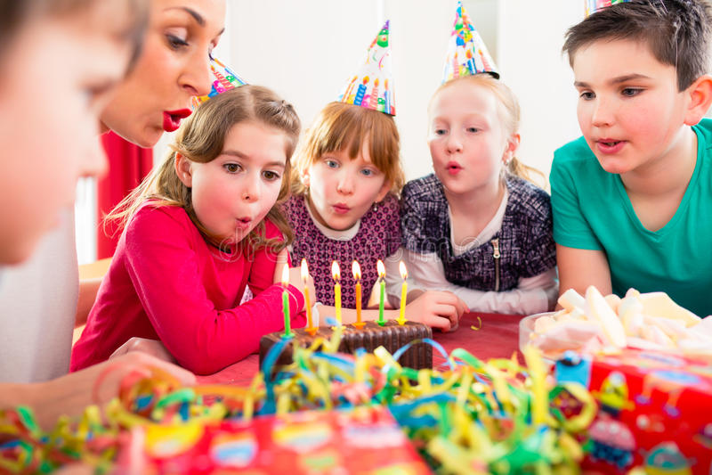 Child on birthday party blowing candles on cake. Being helped by friends and the mother royalty free stock photos