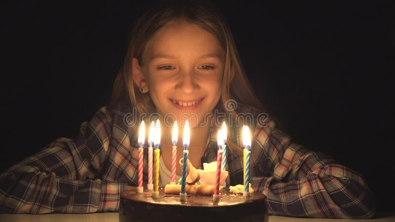 Child Birthday Party Blowing Candles in Night, Kid Celebrate with Cake in Dark.  royalty free stock images