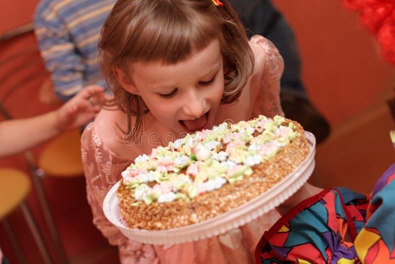 Child bites birthday cake stock photography