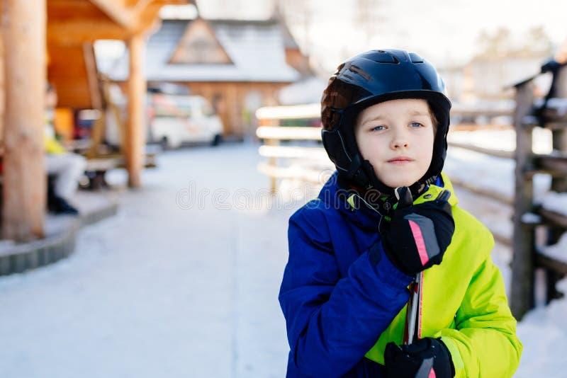 Child in a black ski helmet holding his skis royalty free stock photo