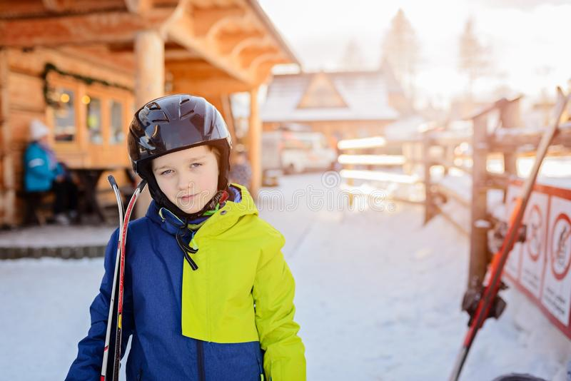 Child in a black ski helmet holding his skis stock images