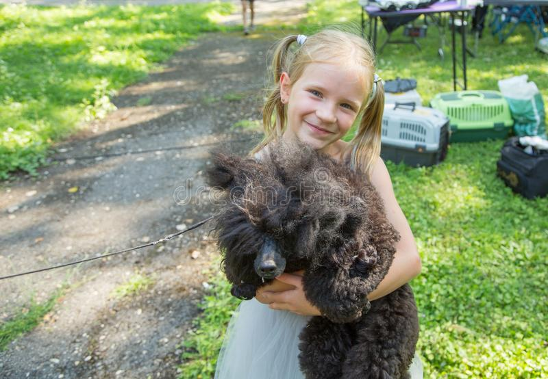 Child blond girl lovingly embraces his pet Poodle dog. Friendship. Child blond girl lovingly embraces his puppy pet Poodle dog. Friendship royalty free stock images
