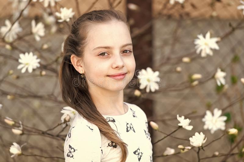 Child with blossoming flowers outdoor. Little girl on floral blossom in spring. Beauty kid with fresh look and long hair. Spring, easter and holidays royalty free stock photography