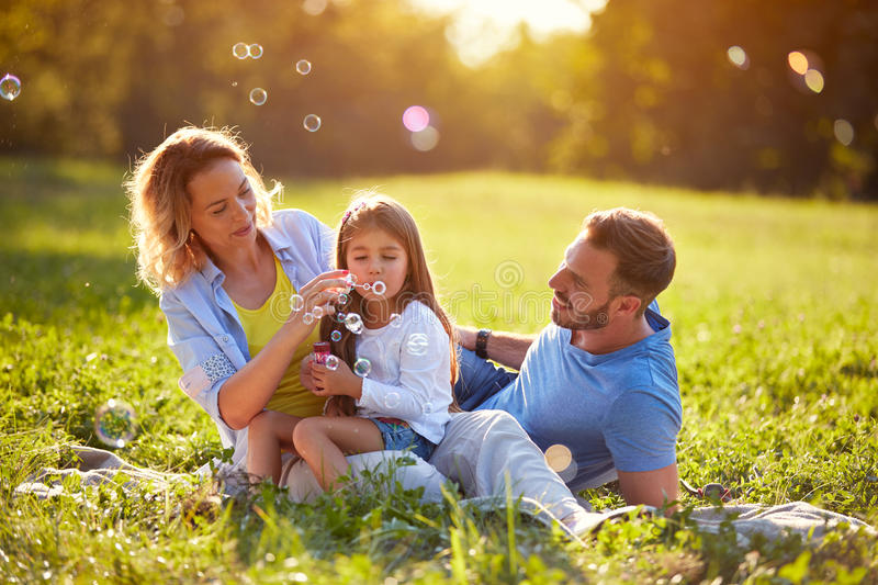 Child blow soup foam and make bubbles in nature. Female child blow soup foam and make bubbles in nature stock photography