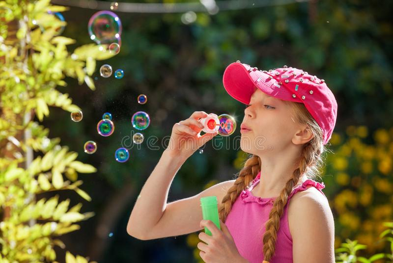Child blowing bubbles outdoors stock image