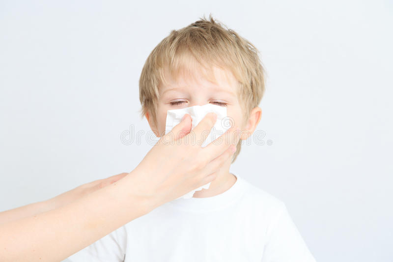Child blowing his nose royalty free stock photos