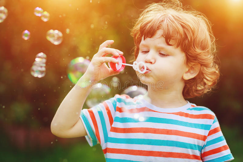 Child blowing soap bubbles in summer park. stock image