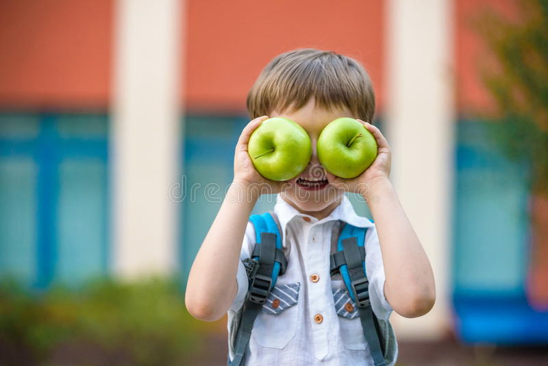 Child with book and green apple outdoors stock image