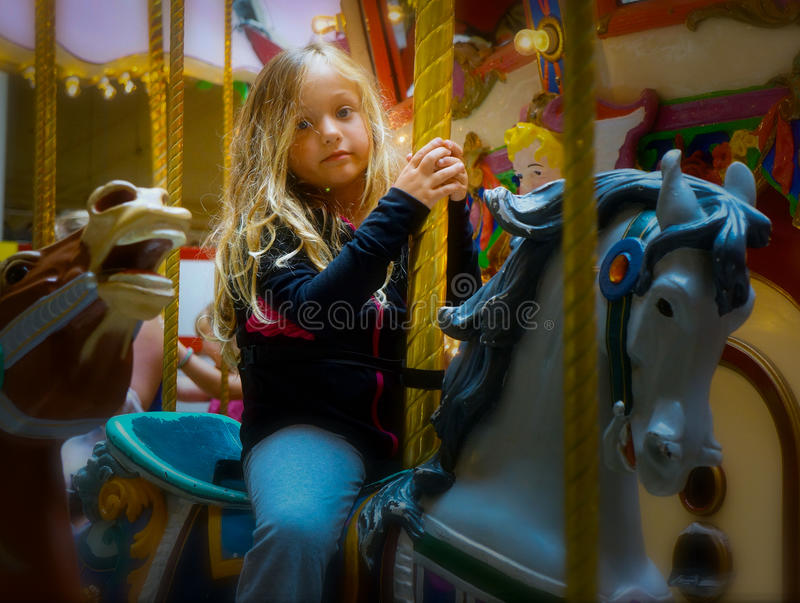 Child on Merry Go Round. Captured this little girl`s bored expression as she rides the slow moving Merry-go-round. Think she would prefer the fun of a faster stock photo
