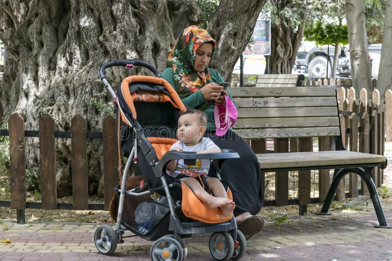 A child bored sitting in a baby stroller. A female mother dressed in traditional Muslim clothing using a smartphone while walking royalty free stock images