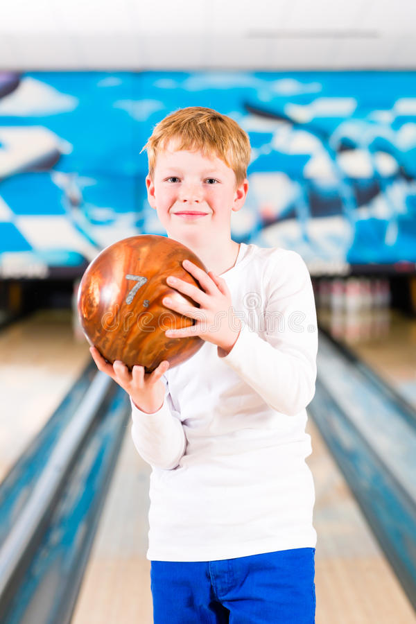 Child bowling with ball. In alley stock images