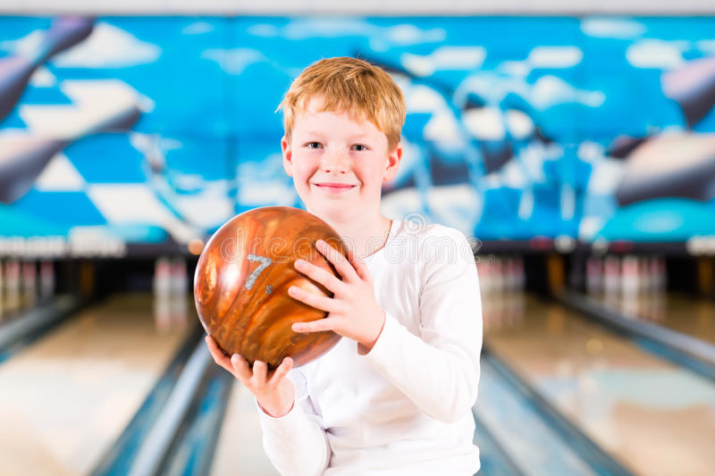 Child bowling with ball. In alley royalty free stock photos