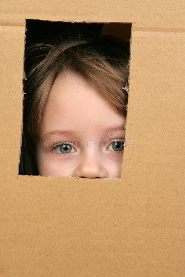 Child in box. Young girl looking from brown carton box royalty free stock photo
