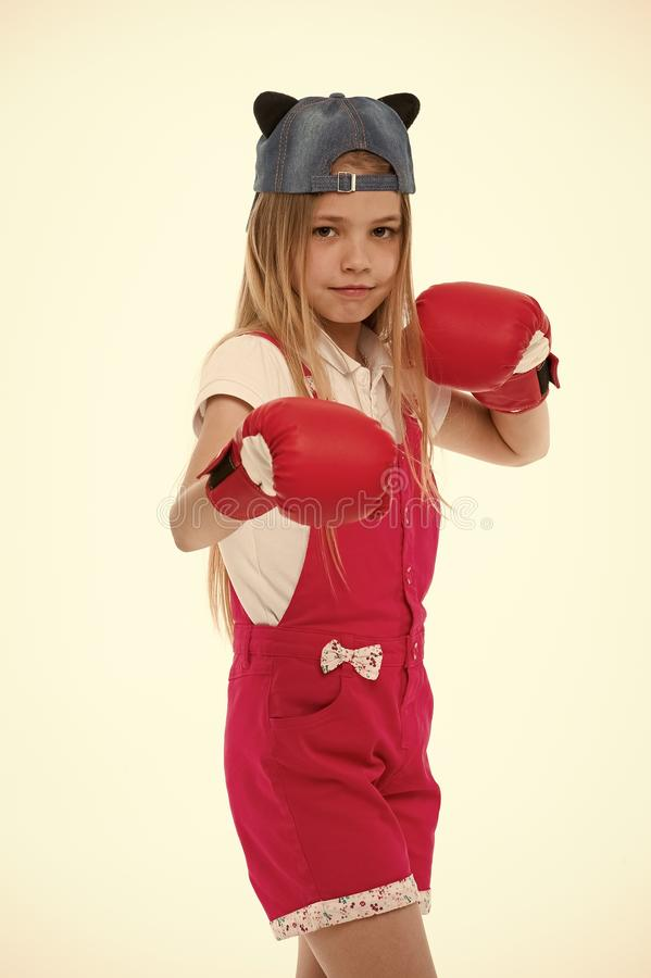 Child in boxing gloves isolated on white. Little girl before training or workout. Kid athlete in fashionable cap. Fashion, style and trend. Sport activity and stock photography