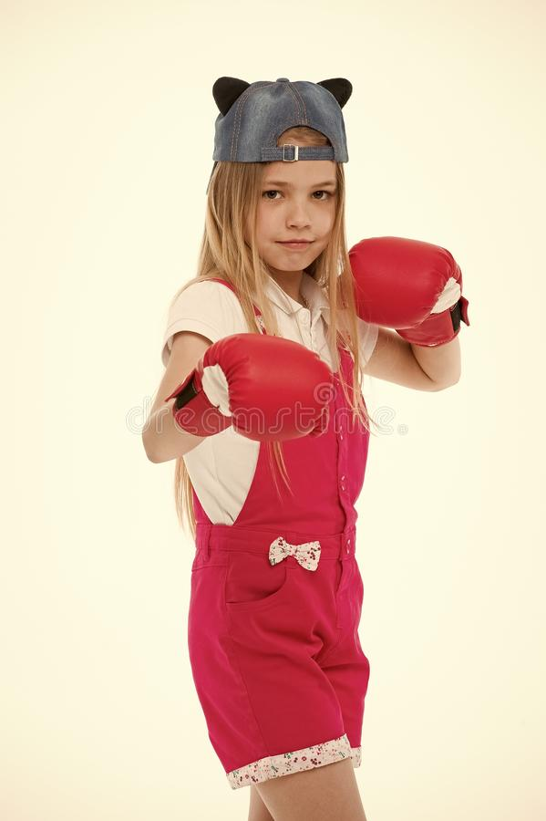 Child in boxing gloves isolated on white. Little girl before training or workout. Kid athlete in fashionable cap. Fashion, style and trend. Sport activity and royalty free stock photography
