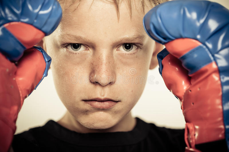 Child with boxing gloves and serious expression royalty free stock images