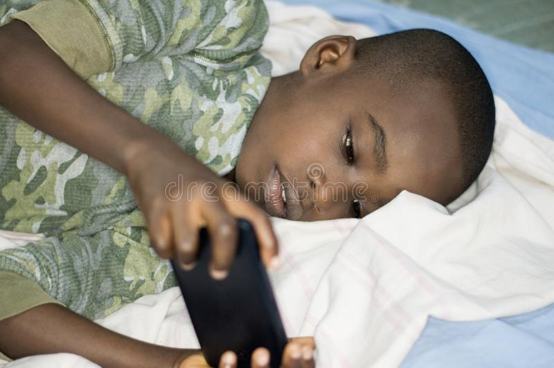 Child boy in bed with smartphone stock photo