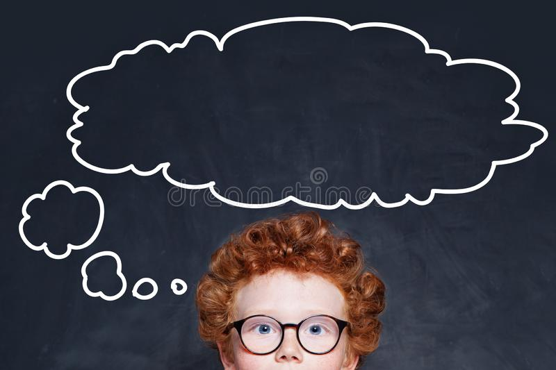 Child boy and big empty speech clouds bubbles on blackboard stock image