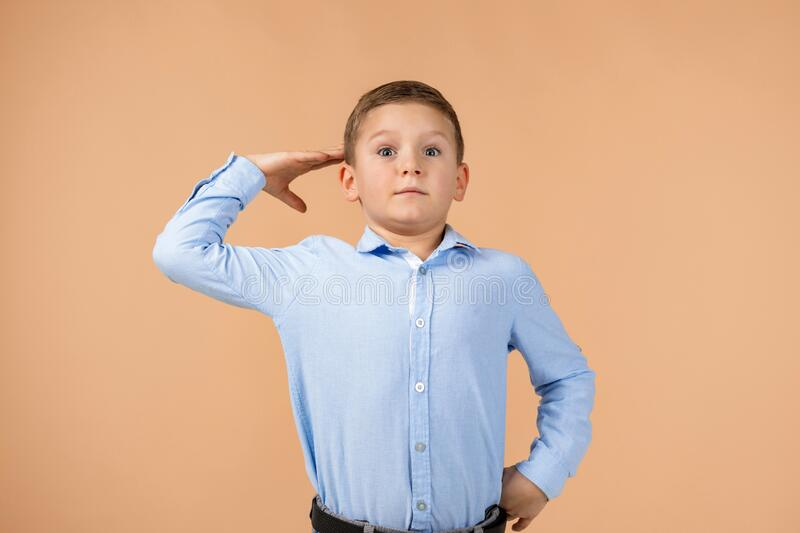 Child boy in blue shirt showing a saluting gesture royalty free stock images